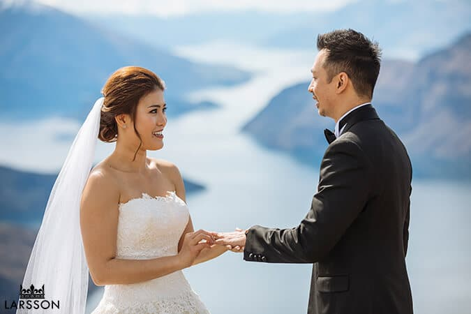 Bride and groom exchanging Cartier rings on Coromandel peak