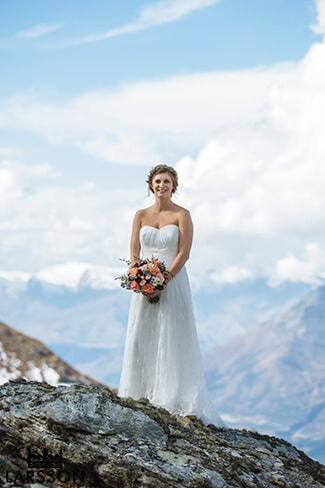 Mountaintop wedding, bride wears strapless lace gown. Destination heli wedding Queenstown
