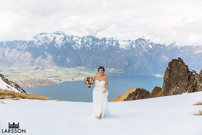 Bride stands in snow during Spring wedding in Queenstown. Destination heli wedding Queenstown