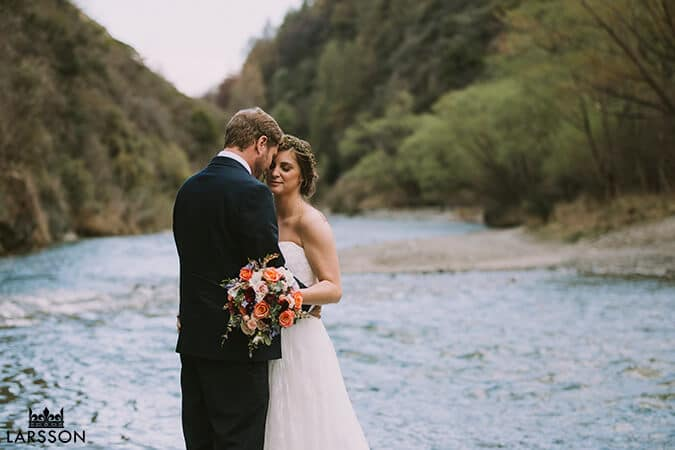 Bride and groom stand on the banks of the arrow river. Queenstown