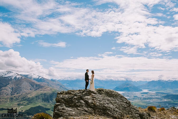 Bride and groom stand on the Pisa ranges during wedding ceremony and photos. Destination Heli weddings Wanaka