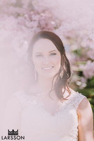 bride stands in front of blossoms on wedding day in Wanaka.Destination Heli weddings Wanaka