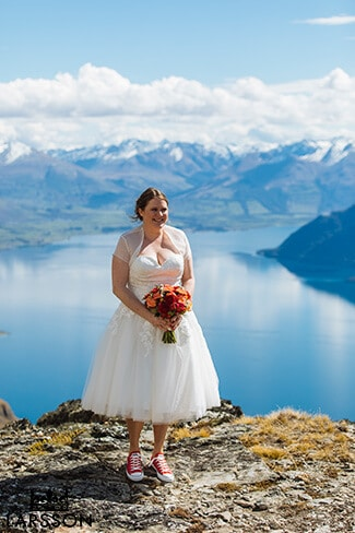 Bride has beautiful bright spring bouquet to match her red converse wedding shoes.Destination Heli wedding Queenstown