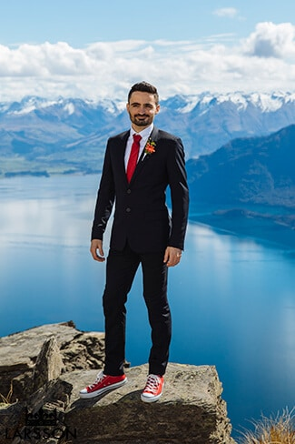 French groom stands on The Ledge. Wedding photos destination Heli wedding Queenstown