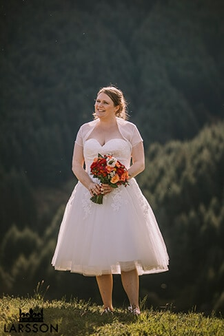 bride stands on grassy hill with spring bouquet. Destination Heli wedding Queenstown