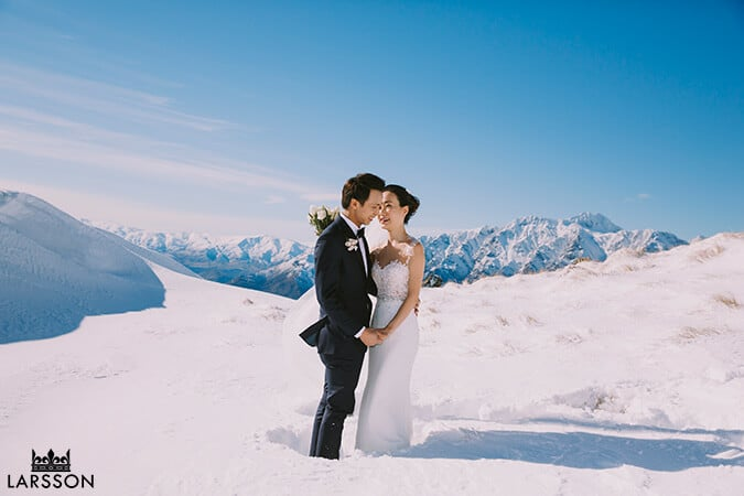 bride and groom stand in deep snow. Destination heli pre wedding photoshoot Queenstown