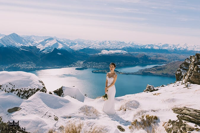 Bride stands on the Ledge for Pre Wedding photoshoot. Destination heli wedding Queenstown