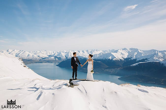 Bride and groom have Pre Wedding photoshoot on The Ledge. Destination heli wedding Queenstown